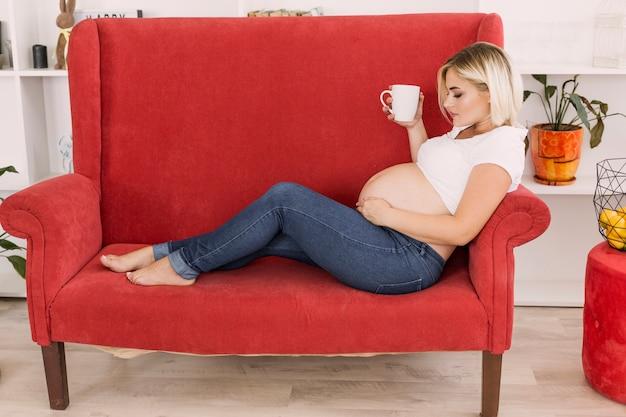 Long shot mulher grávida sentada no sofá