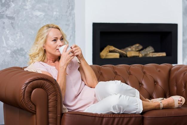 Long shot senhora loira bebendo uma xícara de café