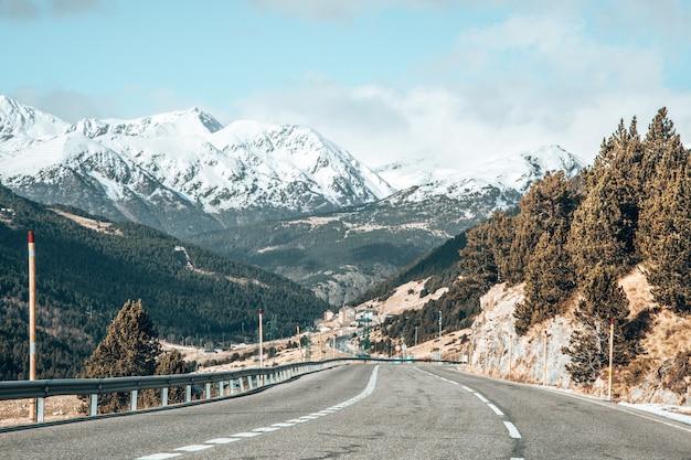 Longa estrada cercada por altas montanhas com topos cobertos de neve