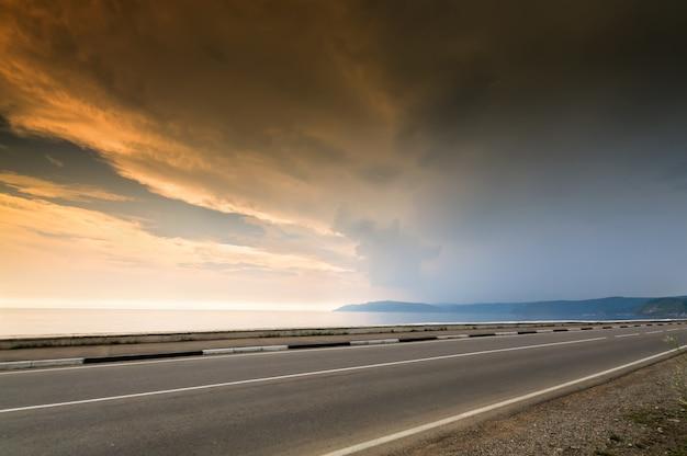 Longa estrada e mar, lago ou linha do oceano na hora por do sol com céu nublado
