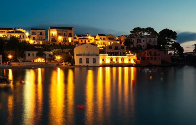 Longa exposição da bonita cidade velha à beira-mar ao pôr do sol com barcos na baía.