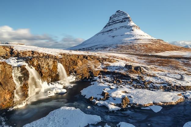 Longa exposição da montanha kirkjufell sob céu claro durante a manhã de inverno