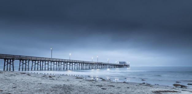 Longa exposição de um píer de madeira no mar na califórnia à noite