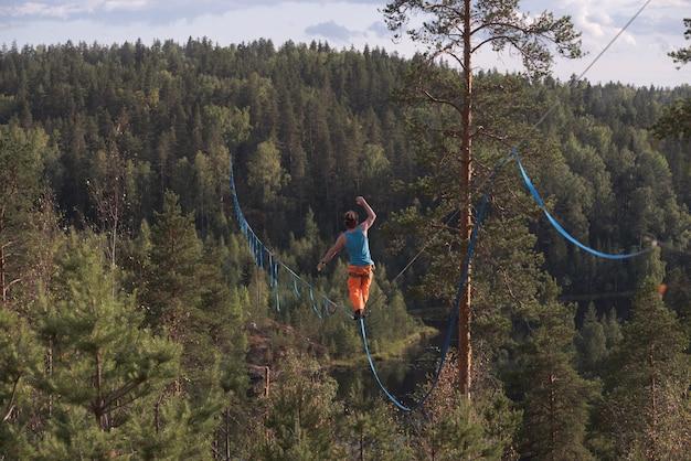 Longa linha alta sobre a floresta. equilibrista na corda bamba