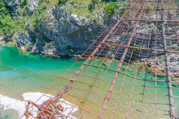 Longa ponte de ferro suspensa e extrema sobre o rio