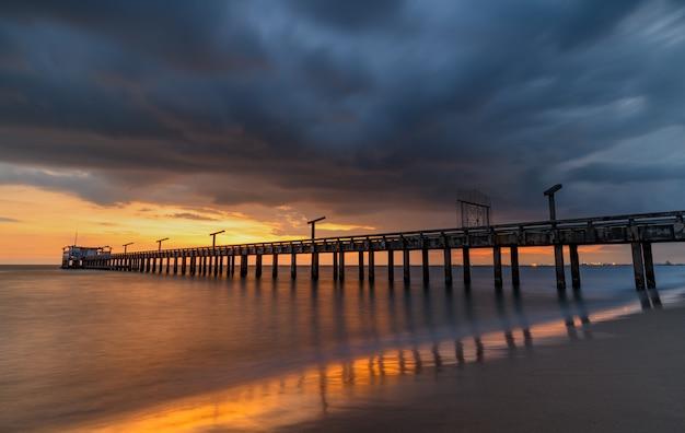 Longa ponte sobre o mar no pôr do sol com iluminação suave e quente e sombra escura nublada