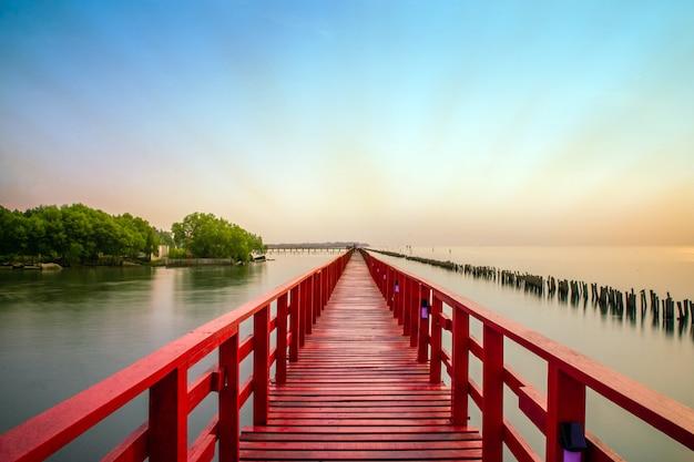 Longa ponte vermelha árvore do céu da luz solar no mar da praia, ponte vermelha samut sakhon tailândia