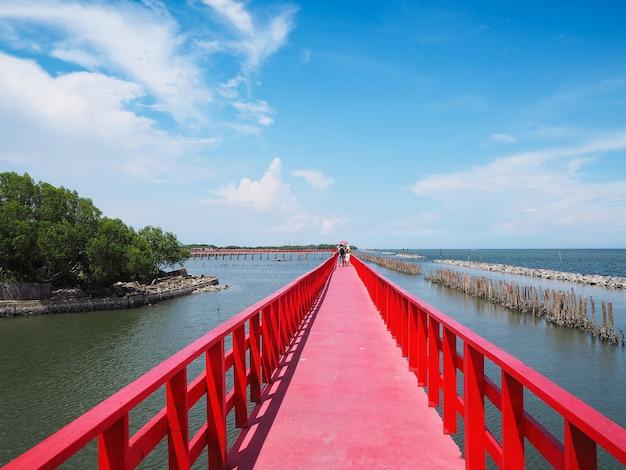 Longa ponte vermelha cruza a praia do verão contra o fundo do céu azul na província de samutsakhon, tailândia.