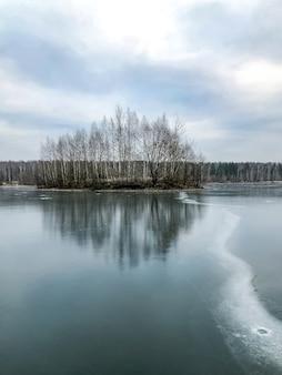 Longa rachadura no gelo azul transparente de um lago congelado com árvores sem folhas em uma pequena ilha na paisagem de inverno do horizonte