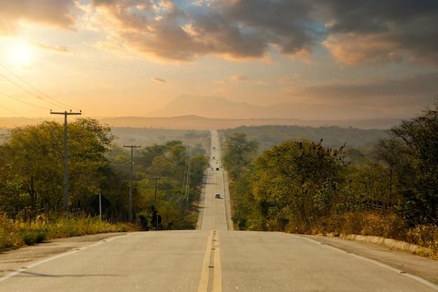 Longa rodovia ladeada de árvores no interior com um céu colorido à tarde