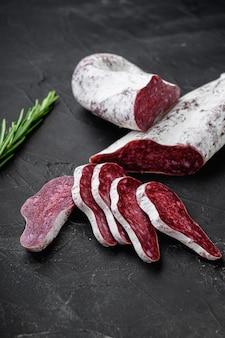 Longaniza, salame tradicional salame espanhol na superfície texturizada preta.
