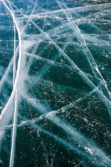 Longas rachaduras no gelo transparente do lago baikal. muitas rachaduras no gelo espesso. orientação vertical.