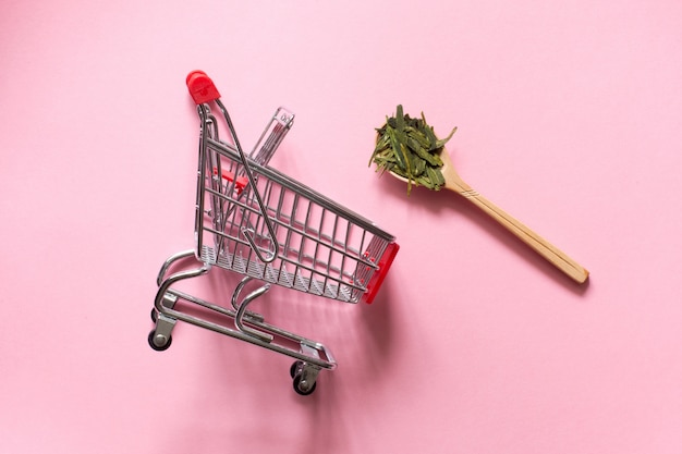 Longjing chá verde da folha chinesa em uma colher em um fundo cor-de-rosa. carrinho de carrinho de compras.