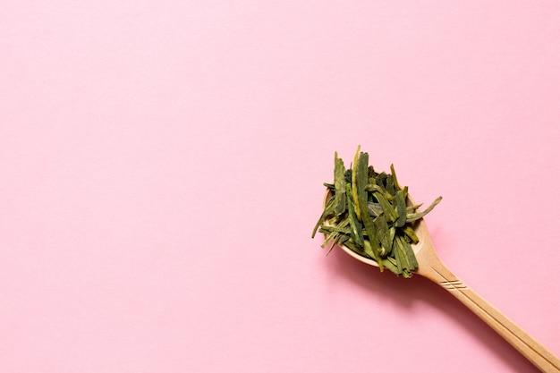 Longjing chá verde da folha chinesa em uma colher em um fundo cor-de-rosa.