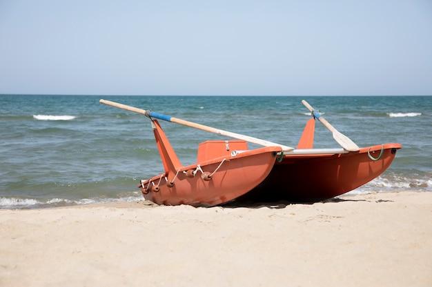 Longo barco a remo à beira-mar