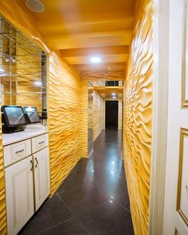Longo corredor com paredes amarelas e portas de teto branco