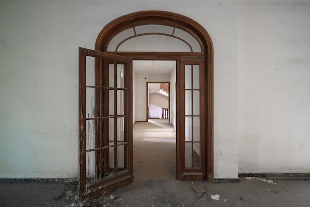 Longo corredor de uma antiga mansão abandonada com portas