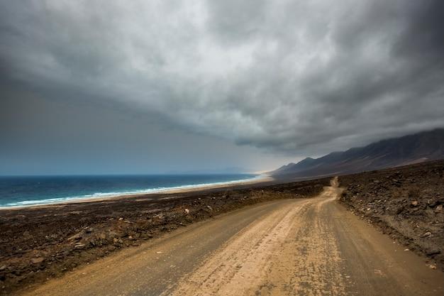 Longo infinito caminho fora da estrada, praia selvagem e montanhas, lugar alternativo de destino para as férias do viajante perdido no desejo de viajar explorando o mundo de maneira diferente bela paisagem com o oceano