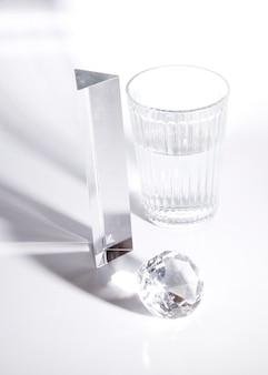 Longo prisma; diamante e copo de água na luz do sol com sombra no fundo branco