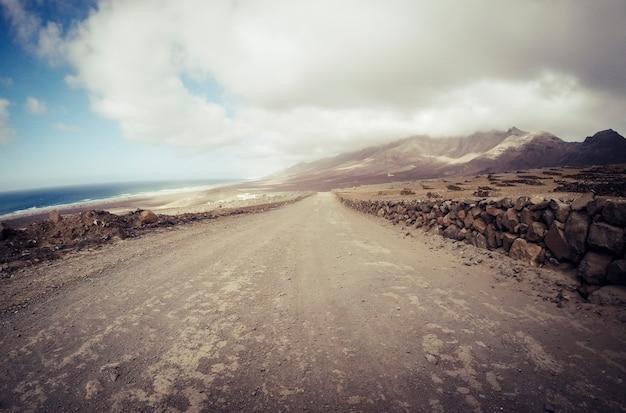 Longo terreno fora de estrada, caminho de estrada visto do nível do solo com montanhas e vista para o mar