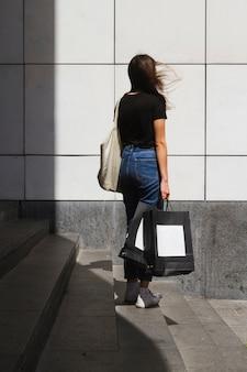 Longo tiro moda mulher com um saco de compras por trás