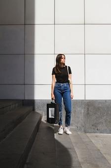 Longo tiro moda mulher posando com uma sacola de compras