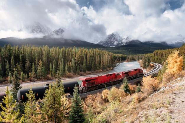 Longo trem de carga vermelho na ferrovia passando pelo vale do outono com a montanha na curva de morant