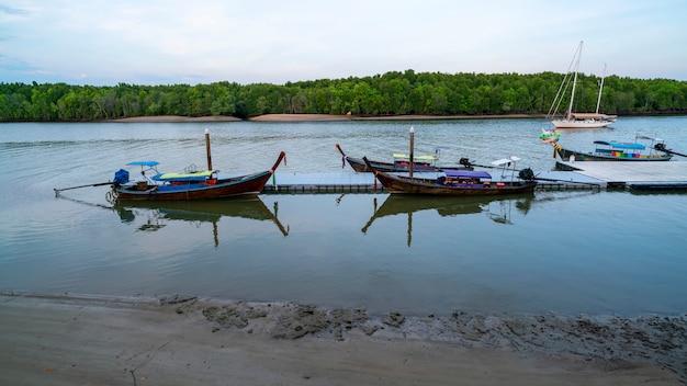 Longtail barco com reflexo no mar bela manhã nascer do sol sobre mar e manguezal em phang