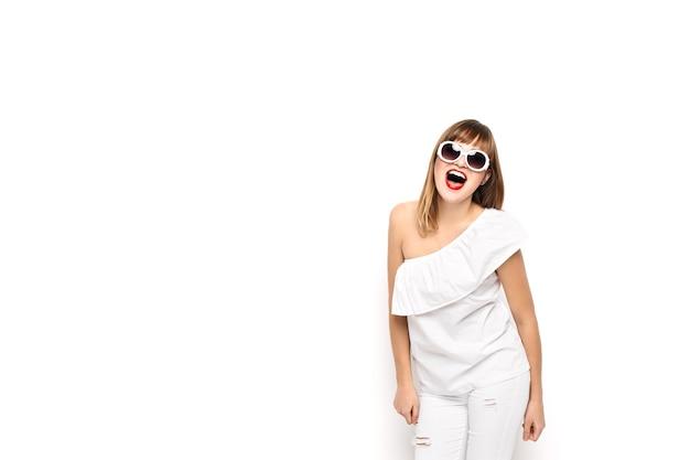 Look de alta moda. glamour elegante modelo de mulher jovem e bonita com lábios vermelhos em um pano branco brilhante de verão moderno