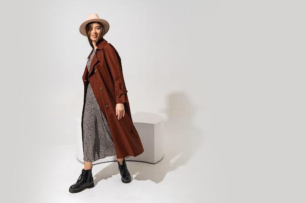 Look de moda winer. modelo moreno elegante com casaco marrom e chapéu bege posando