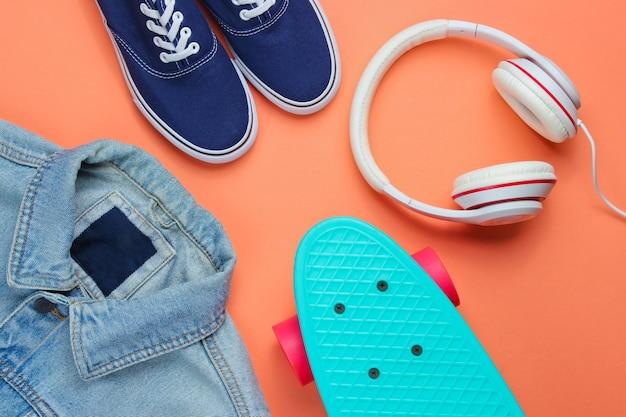 Look moderno da moda. jaqueta jeans, skate, tênis, fones de ouvido em fundo laranja. vista do topo. postura plana