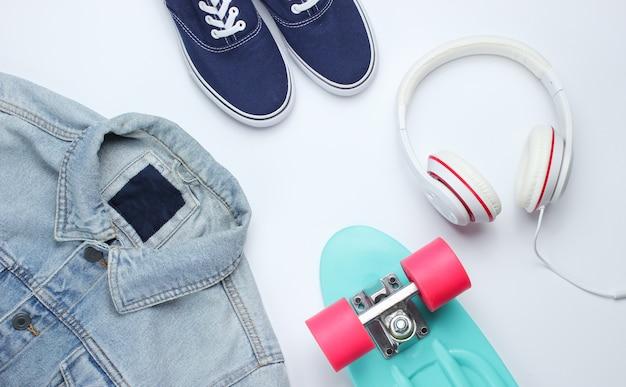 Look moderno da moda. jaqueta jeans, skate, tênis, fones de ouvido em um fundo branco. vista do topo. postura plana