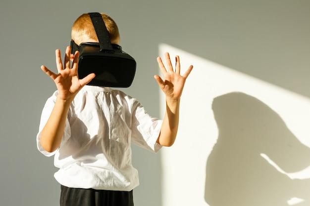 Lookg de menino espantado um óculos de realidade virtual e gesticulando com as mãos isoladas no branco