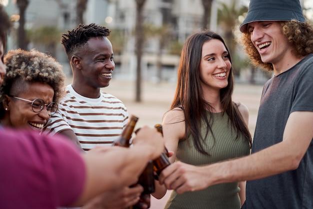 Looks de cumplicidade entre um grupo de jovens brindando com cerveja ao pôr do sol