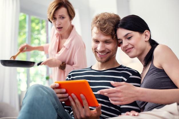Loot nele. mulher alegre e simpática apontando para a tela do tablet enquanto está sentada com o marido