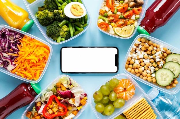Lote de comida cozida em uma variedade de recipientes com smartphone em branco