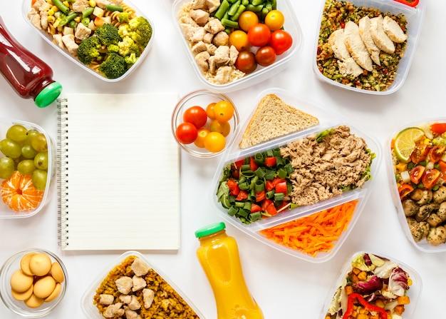Lote de comida cozida na composição de recipientes com caderno vazio