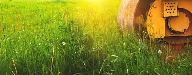 Lote de terreno para canteiro de obras, banner com maquinário pesado ao pôr do sol, fundo de campo verde, foto do espaço de cópia
