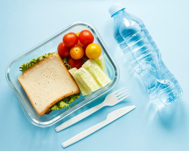Lote os alimentos cozidos em um recipiente com uma garrafa de água