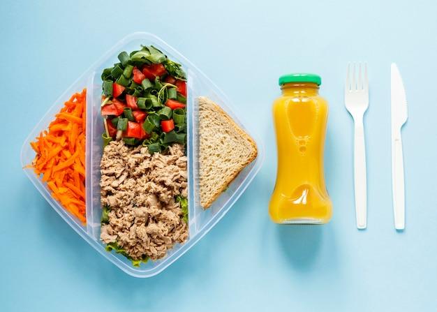 Lote os alimentos cozidos no recipiente com uma garrafa de suco de laranja