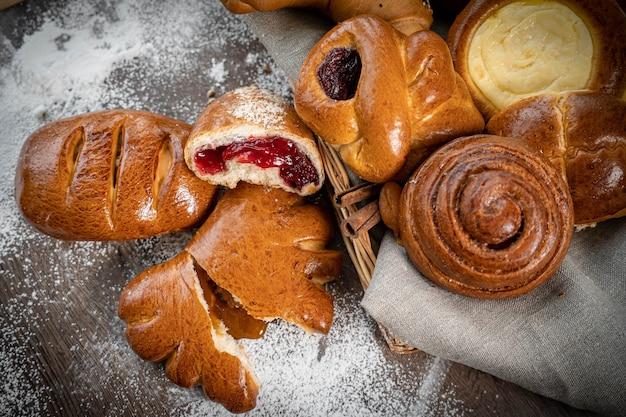 Lotes de pão fresco em uma cesta e uma tábua com farinha em uma mesa de madeira em estilo vintage rústico