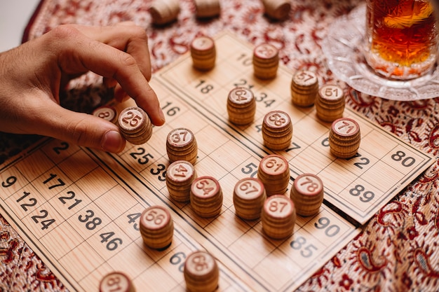 Loto jogo homem coloca número vista lateral para o chá