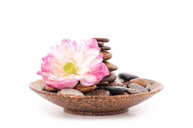 Lótus rosa e pedras em uma tigela de madeira isolada.
