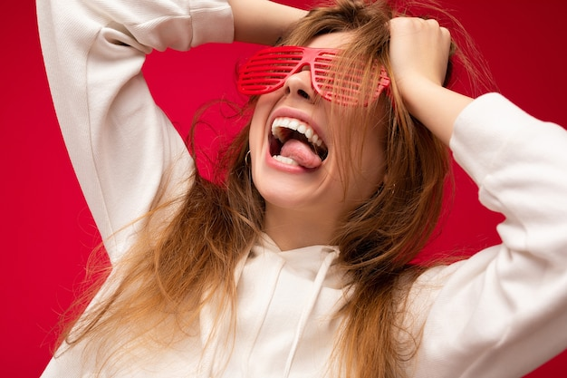 Louca atraente jovem loira isolada sobre fundo colorido, vestindo casual capuz branco e óculos elegantes, se divertindo e mostrando a língua.