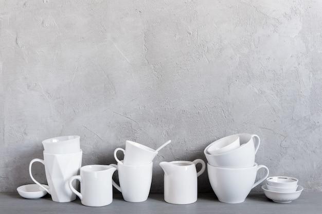 Louça branca em cima da mesa contra a parede cinza texturizada