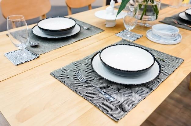 Louça cerâmica moderna na sala de jantar com conjunto de mesa pronto para uma boa refeição