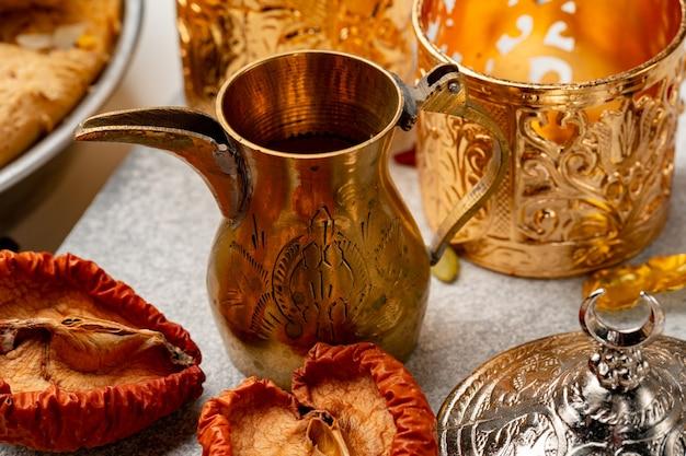 Louça de metal árabe e frutas secas na mesa fecham