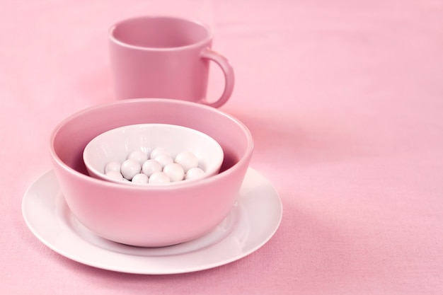 Louça rosa e branca com drageias de açúcar dentro