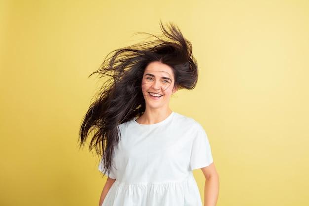 Loucamente feliz, dançando. mulher caucasiana como um coelhinho da páscoa em fundo amarelo do estúdio.