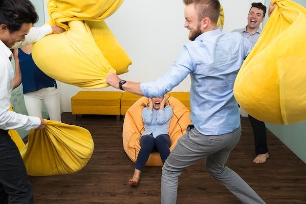 Loucas jovens amigos que lutam travesseiros em casa